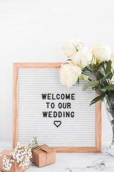 Quadro de boas-vindas para o casamento com caixas de presente e rosas contra o pano de fundo branco