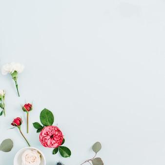 Quadro de borda de flores feito de rosas vermelhas e bege, cravo branco e ramos de eucalipto em fundo azul pastel pálido. camada plana, vista superior