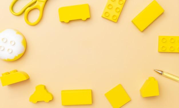 Quadro de brinquedos de crianças em fundo amarelo com brinquedos plano leigos vista superior com centro vazio