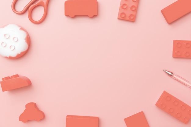 Quadro de brinquedos de crianças em fundo vermelho com brinquedos plano leigos vista superior com centro vazio