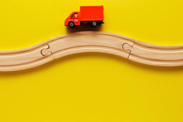Quadro de brinquedos de crianças no backround amarelo, ferrovia de madeira de brinquedo e trem. vista do topo. flatlay. copie o espaço para texto