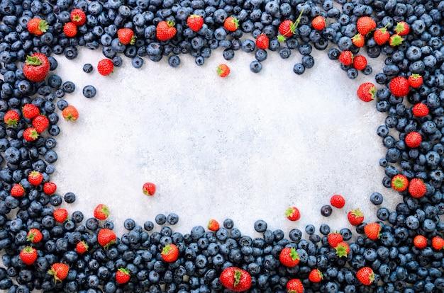 Quadro de comida com mistura de morango, mirtilo. conceito vegan e vegetariano. fundo de bagas de verão