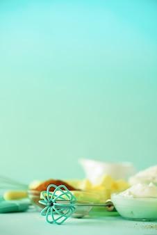 Quadro de comida de padaria, conceito de cozinha. ingredientes de cozimento diferentes - manteiga, açúcar, farinha, leite, ovos, óleo, colher, rolo, escova, batedor