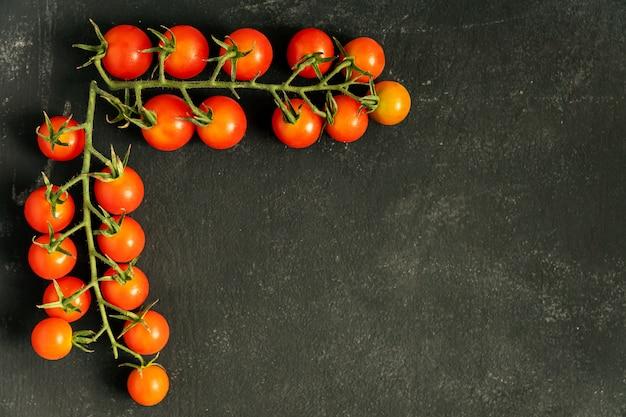 Quadro de comida feito de dois ramos de tomates cereja frescos maduros na parede preta. copie o espaço para seu projeto.