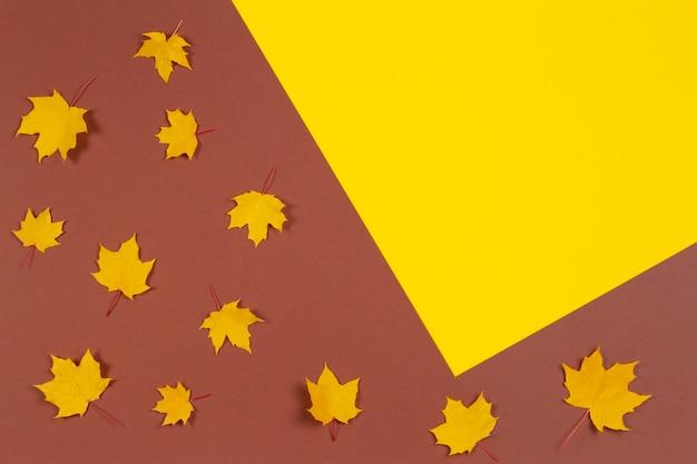 Quadro de composição de outono feito de folhas de bordo de outono em fundo marrom e amarelo
