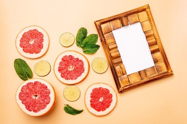 Quadro de conceito de fundo de verão, toranja fatiada, limão, hortelã em fundo laranja