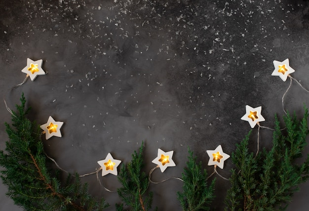 Quadro de conceito de natal ou ano novo com decorações de férias de inverno. fundo escuro com uma guirlanda em chamas. copie o espaço.