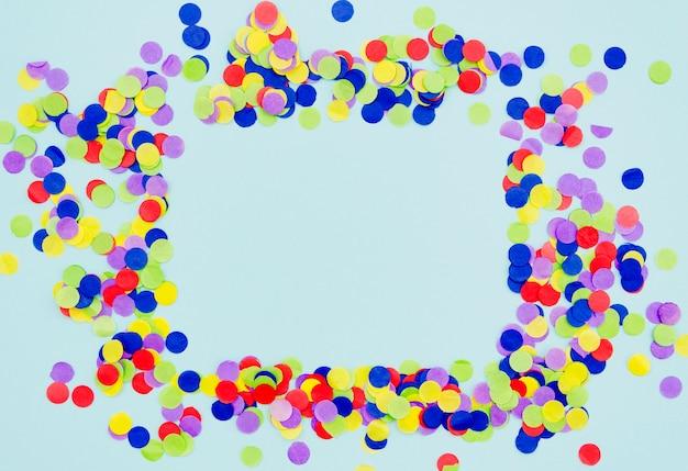 Quadro de confetes coloridos sobre fundo azul