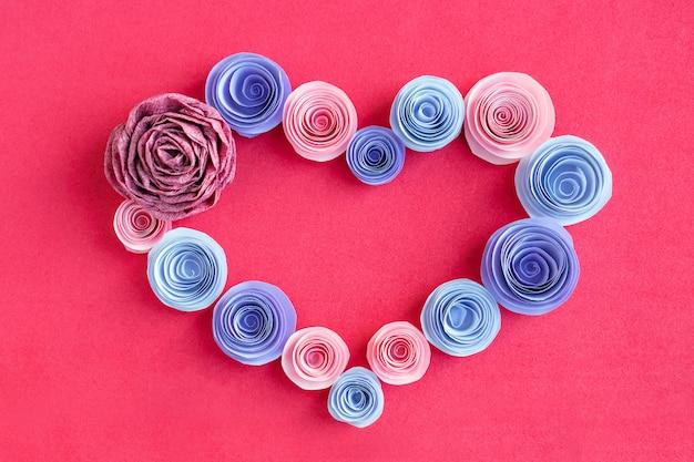 Quadro de coração de flores de papel artesanal em um fundo rosa