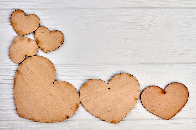 Quadro de corações de madeira e espaço de cópia. corações de madeira compensada com furo na luz de fundo de madeira, espaço para texto. plano de fundo do feriado do dia dos namorados.