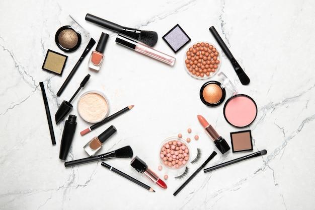 Quadro de cosméticos decorativos e acessórios para maquiagem na parede cinza