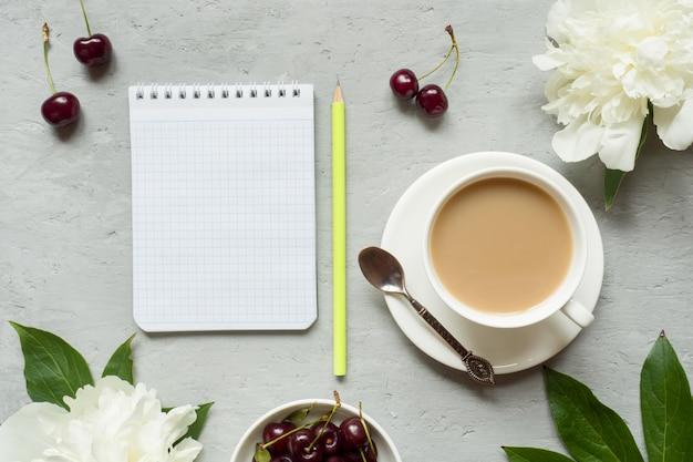 Quadro de creme bolos cereja flores peônia notepad xícara de chá.