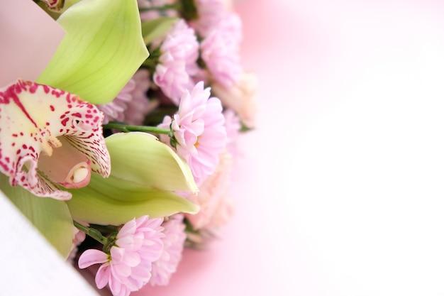 Quadro de crisântemos roxos e rosa, orquídea e flores diferentes em fundo rosa.