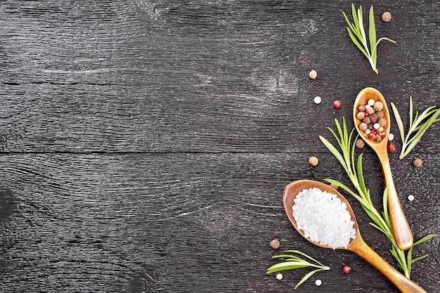 Quadro de duas colheres com sal e ervilhas de pimentão, alecrim no fundo preto da placa de madeira