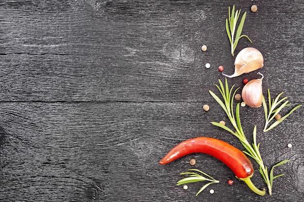 Quadro de ervilhas de pimenta colorida, alecrim fresco, vagem de pimenta vermelha e dois dentes de alho em uma placa de madeira preta