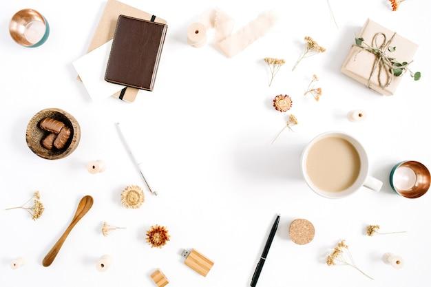 Quadro de espaço de trabalho do blogger ou freelancer de caneca de café, caderno, doces e acessórios em fundo branco. mesa de escritório em casa de estilo minimalista em marrom horizontal, vista superior. conceito de blog de beleza.