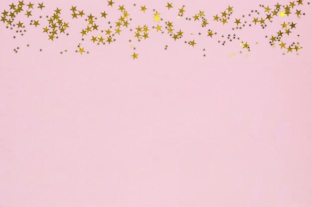 Quadro de estrelas douradas glitter confetes em fundo rosa.