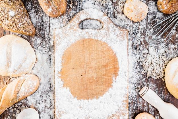 Quadro de farinha branca na tábua de cortar rodeado com pão pães