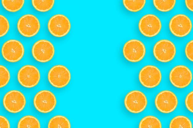 Quadro de fatias de laranja cítricas sobre fundo azul brilhante