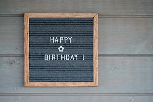 Quadro de feltro com texto em inglês feliz aniversário em uma parede de madeira cinza
