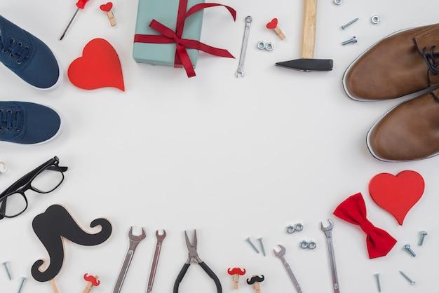 Quadro de ferramentas, sapatos de presente e homem na mesa