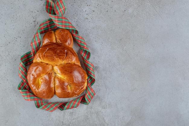Quadro de fita em torno de um pão doce na mesa de mármore.
