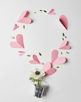 Quadro de flores em um balde e corações de papel com copyspace, plano leigo