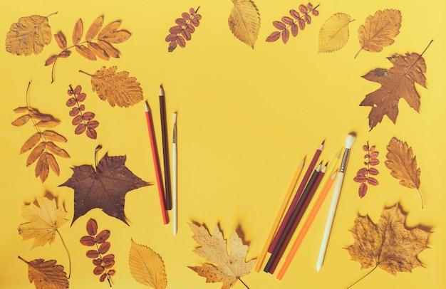 Quadro de folhas coloridas em fundo amarelo com espaço de cópia. conceito de escola