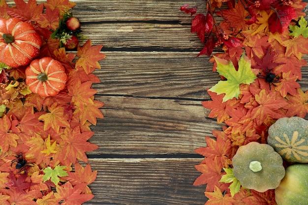 Quadro de folhas de outono e fundo de madeira velho de abóboras com espaço de cópia