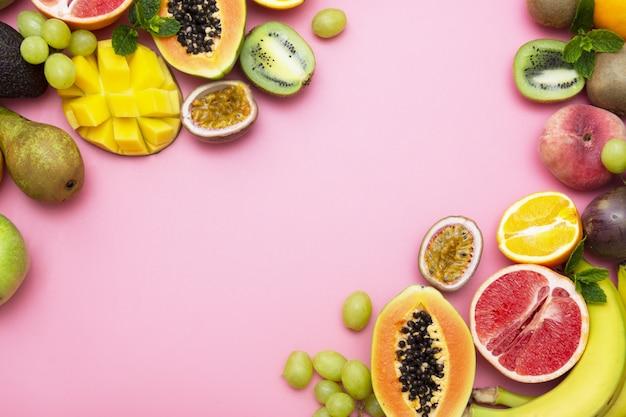 Quadro de frutas de verão com espaço de cópia sobre fundo rosa. postura plana.
