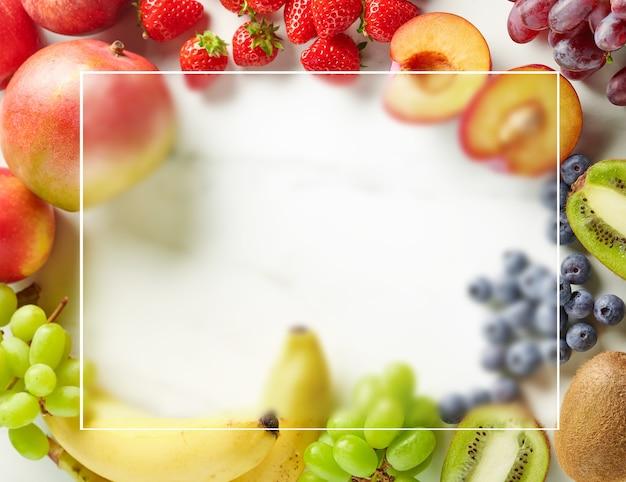 Quadro de frutas frescas e bagas na mesa da cozinha, vista superior através de vidro fosco