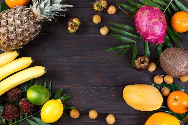Quadro de frutas tropicais com folhas de palmeira sobre um fundo escuro de madeira