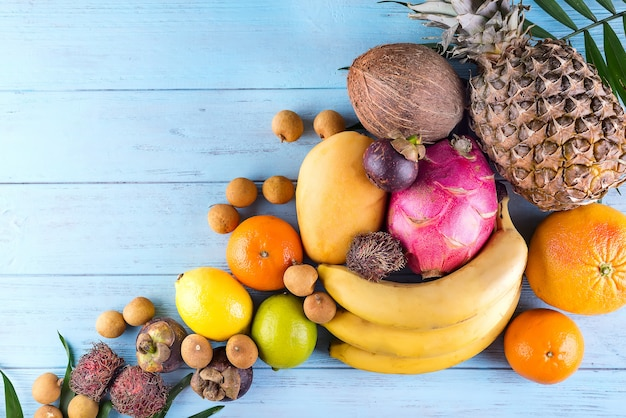Quadro de frutas tropicais do arco-íris saudável com palma deixa na mesa de madeira azul
