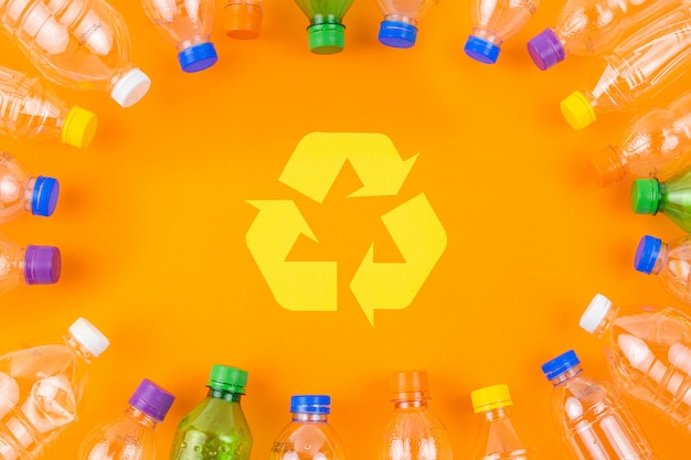 Quadro de garrafas de plástico arredondado e símbolo de reciclagem.