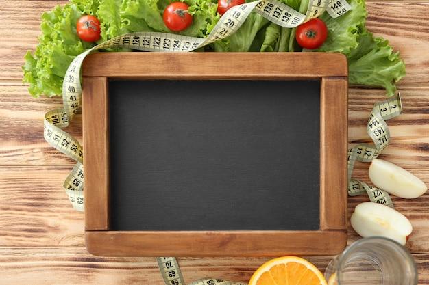 Quadro de giz, comida fresca saudável e fita métrica na mesa de madeira