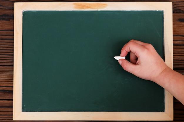 Quadro de giz estudo escolar verde e mão da criança com giz