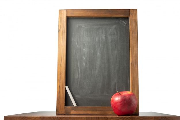 Quadro de giz, giz e maçã em cima da mesa. de volta à escola