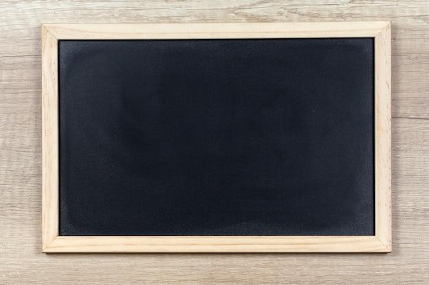 Quadro de giz preto com moldura de madeira.