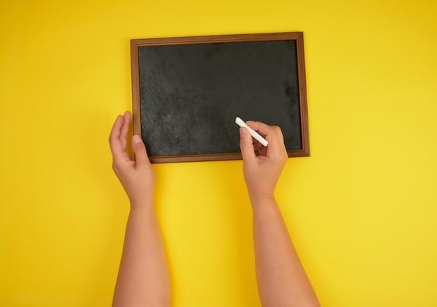 Quadro de giz preto e duas mãos femininas com um pedaço de giz branco