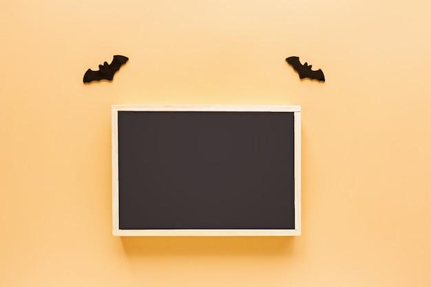 Quadro de giz preto e morcegos em fundo laranja