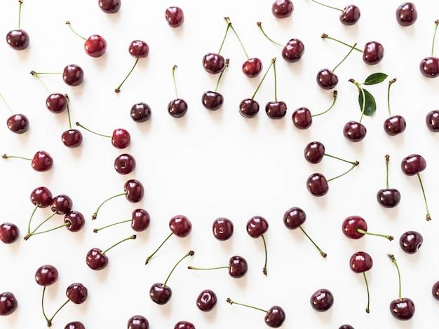 Quadro de grandes bagas maduras de cereja no fundo branco. fundo de comida natural de verão. layout de verão comida criativa. vista do topo. copie o espaço