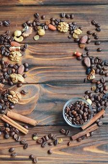 Quadro de grãos de café, passas, nozes e canela em fundo de madeira natural com espaço de cópia para o seu texto