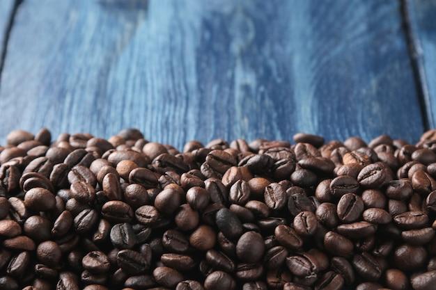 Quadro de grãos de café torrados em uma mesa de madeira azul. espaço para texto