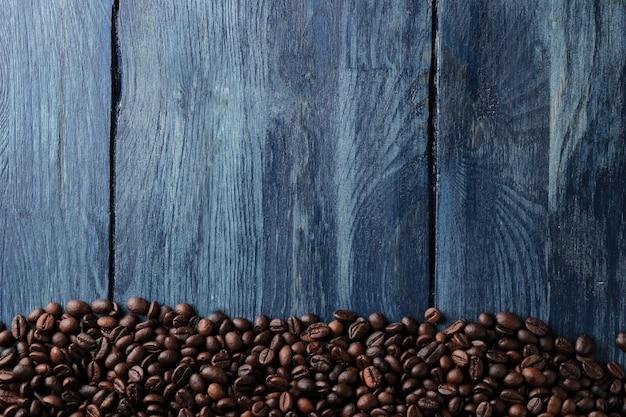 Quadro de grãos de café torrados em uma mesa de madeira azul. vista de cima. espaço para texto