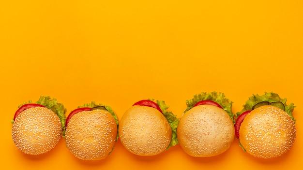 Quadro de hambúrgueres de vista superior com fundo laranja