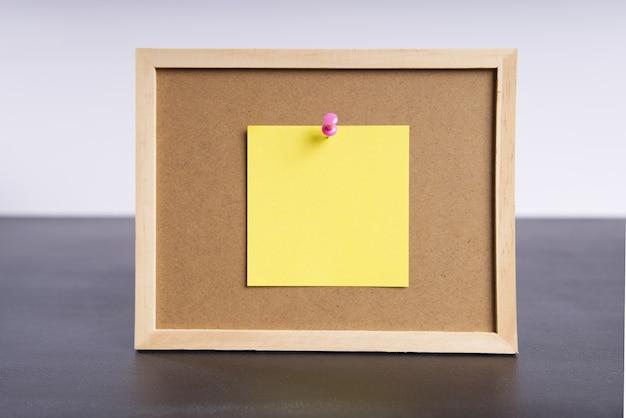 Quadro de informações de escritório com um pedaço de papel amarelo anexado com espaço para texto