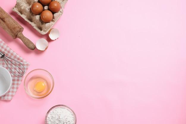 Quadro de ingredientes alimentares com utensílios de cozimento em fundo rosa bebê