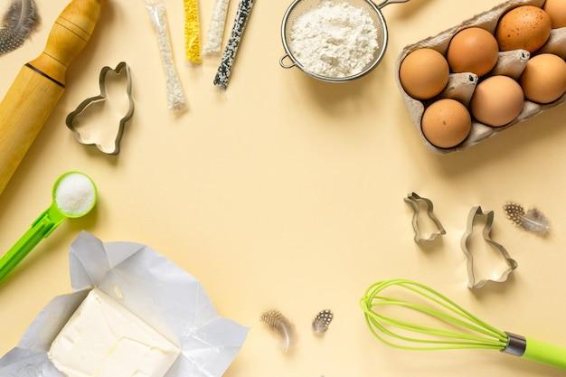 Quadro de ingredientes para panificação de páscoa e utensílios de cozinha. farinha, ovos, manteiga e granulado doce em fundo bege.