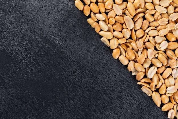 Quadro de layout diagonal de amendoins de vista superior com espaço de cópia em preto
