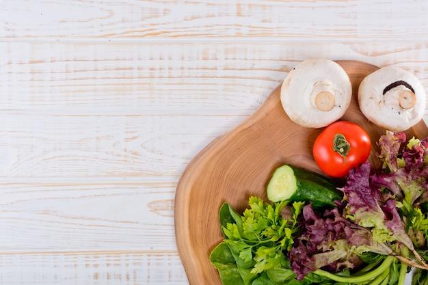 Quadro de legumes frescos, alface, tomate, pepino, cogumelos, salsa, espinafre em um de madeira